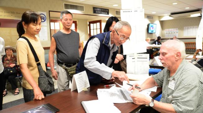 紐約市12日舉行初選,梁先生由家人陪同在法拉盛班杰明王子街老人中心投票站領選票。(記者許振輝/攝影)
