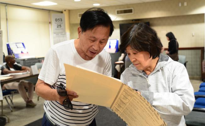 紐約市12日舉行初選,兩位選民在法拉盛班杰明王子街老人中心投票站討論給合意的候選人。(記者許振輝/攝影)