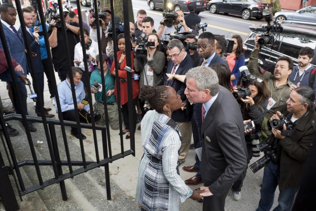 白思豪和妻子麥克雷(Chirlane McCray)走出投票現場親吻。(美聯社)