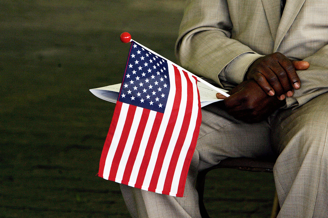一名獅子山公民拿著美國國旗,等待申請歸化為美國公民。(法新社)