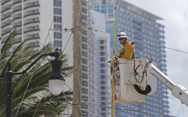圖為工作人員在佛州陽光島海灘搶修電力設備。(TNS)