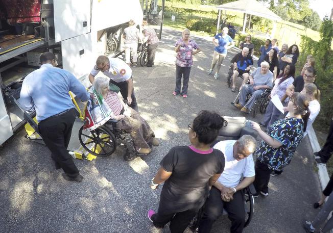 佛州好萊塢丘療養院工作人員和消防人員一同將院中老人轉移到安全場所。(美聯社)