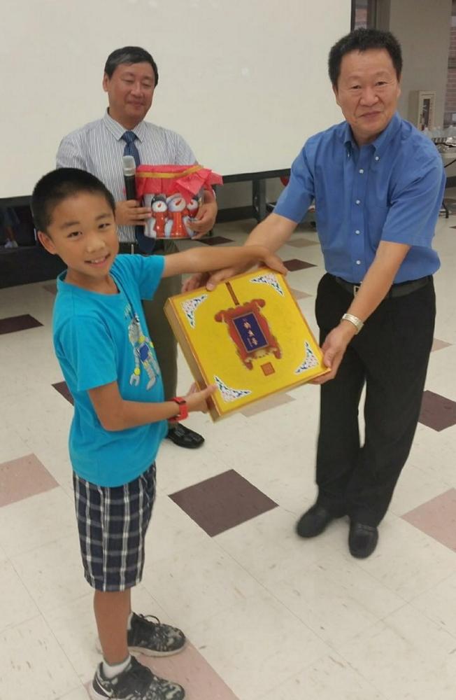 中國駐休士頓總領事館僑務組領事易川(右)贈送釣魚台月餅等,由吳秉誠小朋友(左)代表接受。(塔城華人協會提供)