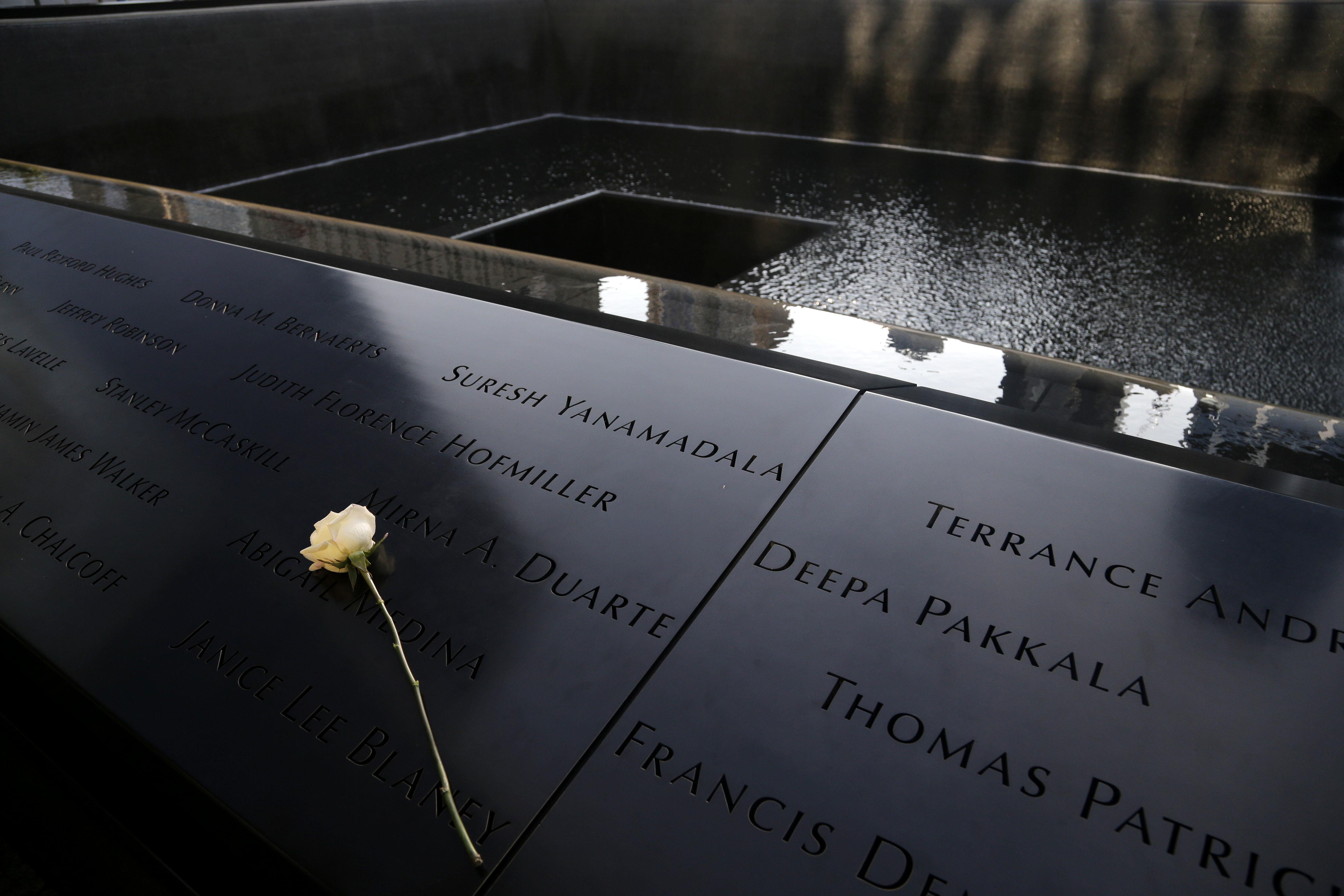 家屬在自己的罹難親人名字上插上玫瑰花悼念。(美聯社)