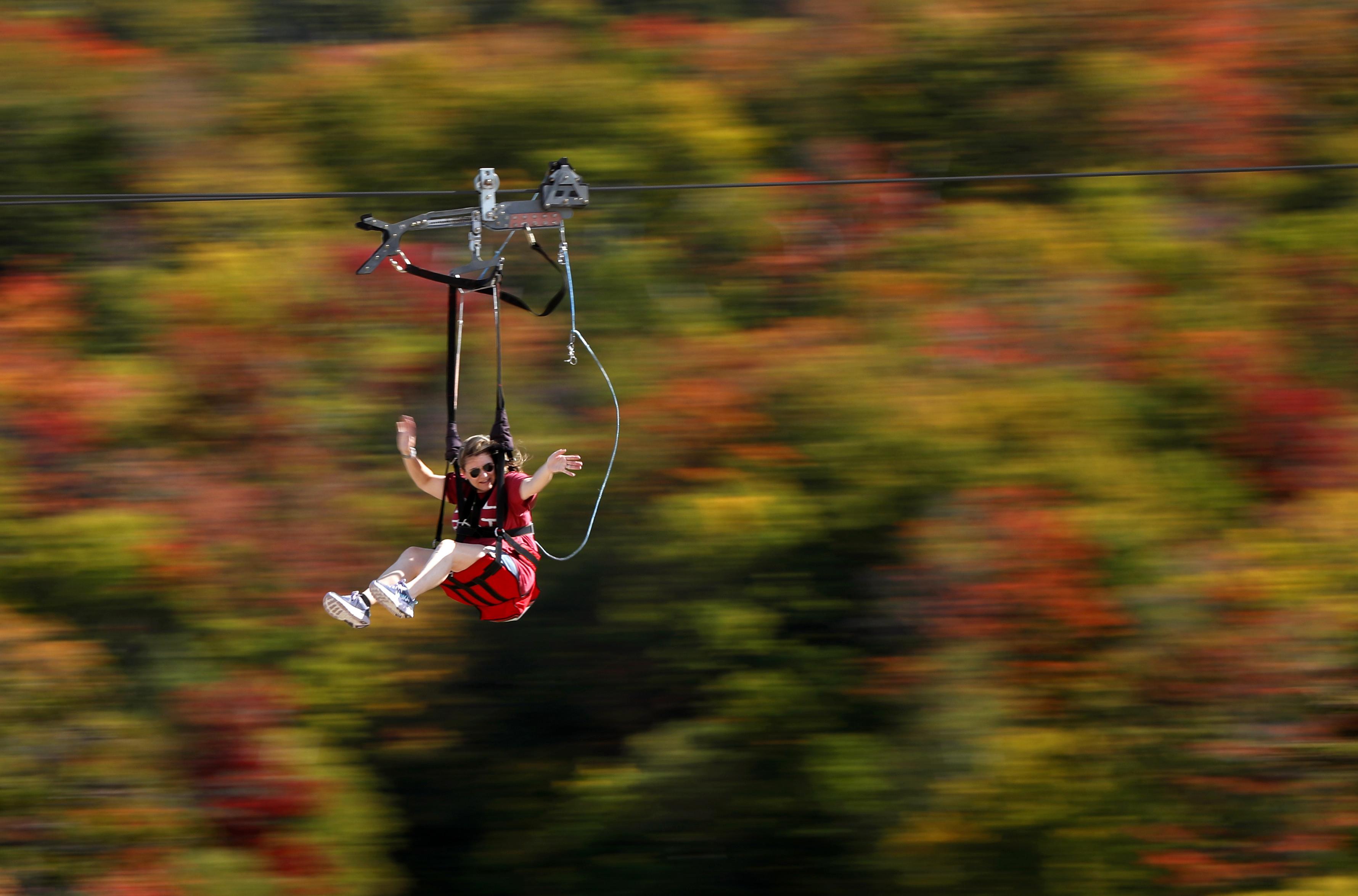 來自麻州的Katie McWalter,23日在新罕布夏的Pinkham Notch的野貓山上玩高空滑索,山中樹葉已有秋意。(美聯社)