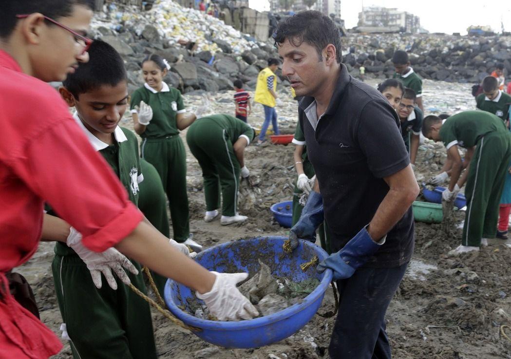 34歲的印度律師沙哈(右)戴上手套,帶領群眾撿拾沙灘垃圾。他們花費98個周末,收集超過500萬公斤的垃圾。(美聯社)