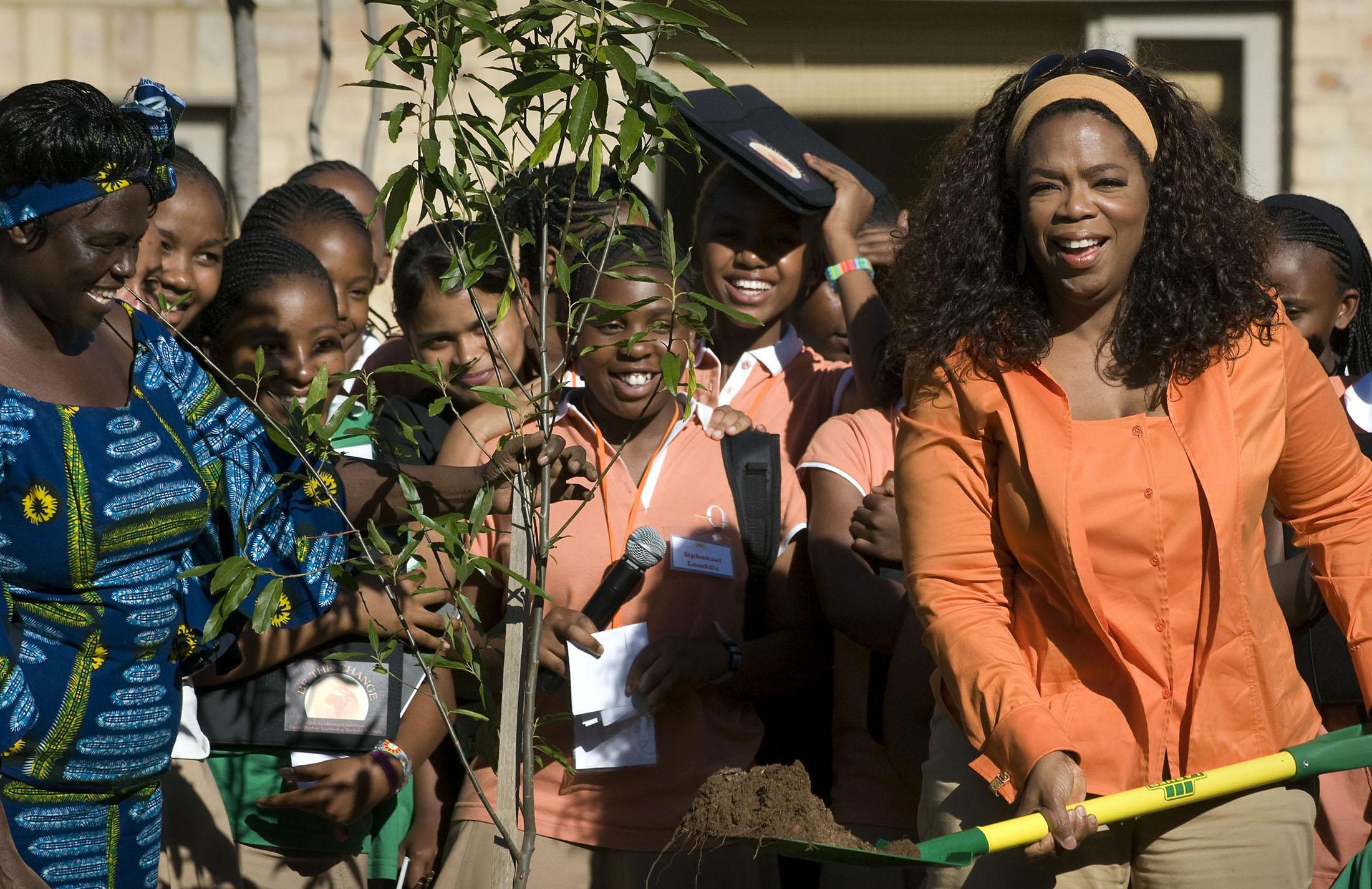 美國電視脫口秀主持人歐普拉.溫芙瑞( Oprah Winfrey,右)、瑪泰(左)及小朋友,2008年11月25日在南非約翰尼斯堡南方的Henley-On-Klip「歐普拉女子領導學校」 (Oprah Winfrey Leadership Academy for Girls)種樹。(美聯社)