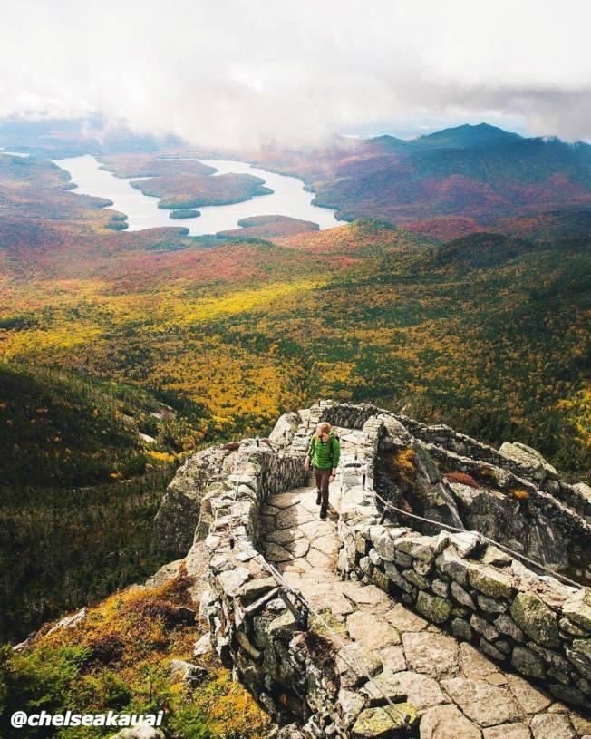 金秋到來,紐約州處處美景,圖為在白面山俯瞰山下八仙湖(Lake Placid)邊的秋色。(取自I Love New York臉書)