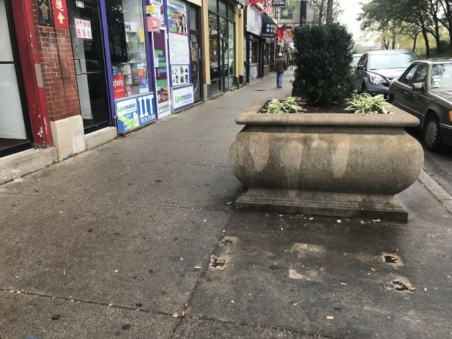 華埠舍麥路與永活街口附近的人行道石椅,地上仍留有拆除後的痕跡,而人行道也明顯乾淨許多。(記者董宇/攝影)