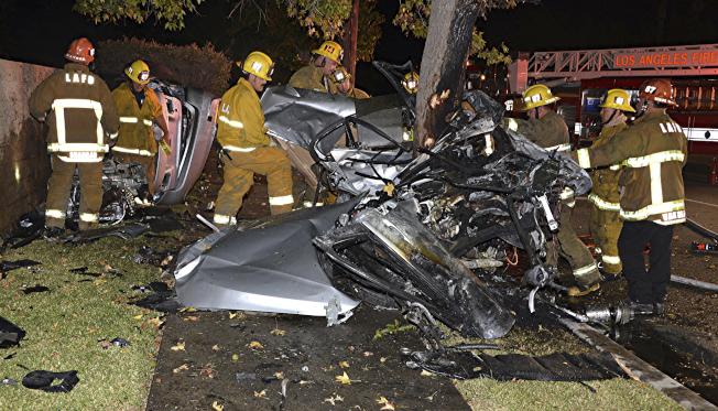 寶馬轎車撞樹後,上下兩半分家,上半部抱樹。(美聯社)