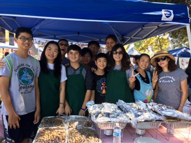 核桃谷學區華人家長會的家長和學生義工們,在歡樂節上以中式美食為學生活動籌款。(記者楊青/攝影)