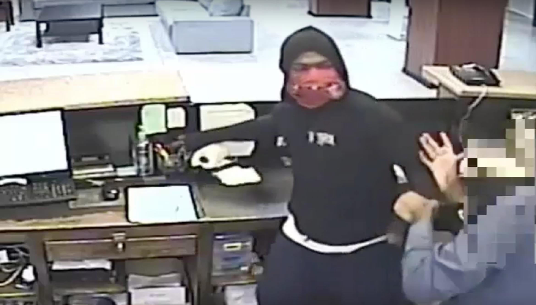 非裔嫌犯見受害者(右)試圖用手保護頭部,拿起桌上筆筒猛擊受害者。(休士頓警局提供)