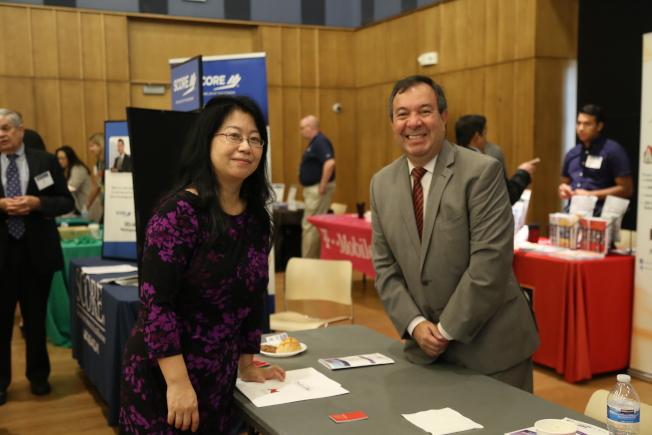 亞美商會在馬州銀泉市政中心,舉辦第8屆亞美企業峰會及商展。商會主席邵欣(左)與商展代表交流業內資訊。(記者羅曉媛/攝影)