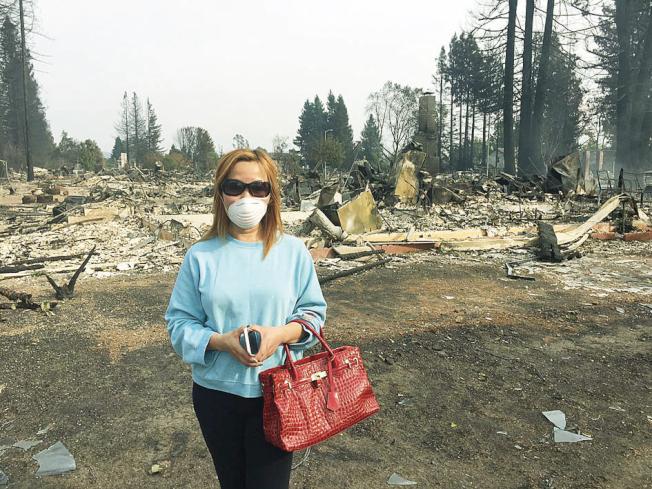 有華人戴著口罩,臉色沉重的在燒毀的房子面前拍照。(丁駿輝供圖)