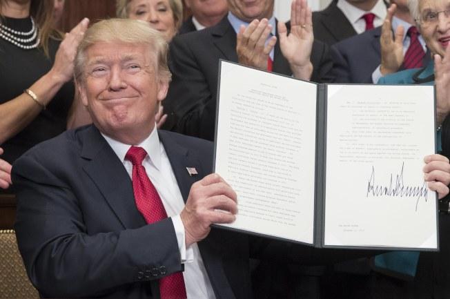 川普簽署行政命令後,高興得舉起來展示。(歐新社)