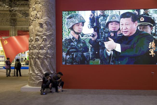 北京舉行的大型成就展的會場,播放習近平持槍的畫面。(美聯社)
