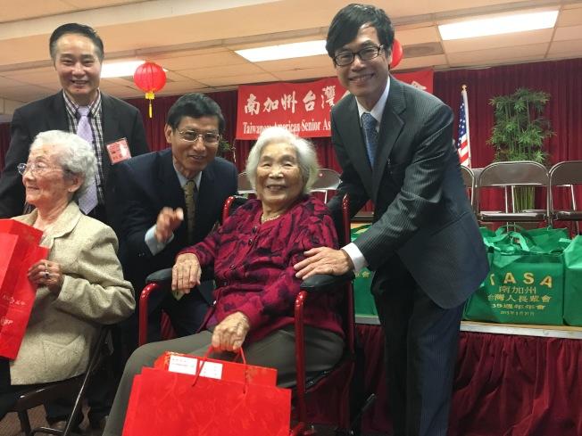 政務委員林萬億(後排中)、洛杉磯僑教中心主任翁桂堂(後排右)一同送禮給105歲黃蔡瑞雲(前排左)、102歲卓許招治女士(前排右)。(記者謝雨珊/攝影)