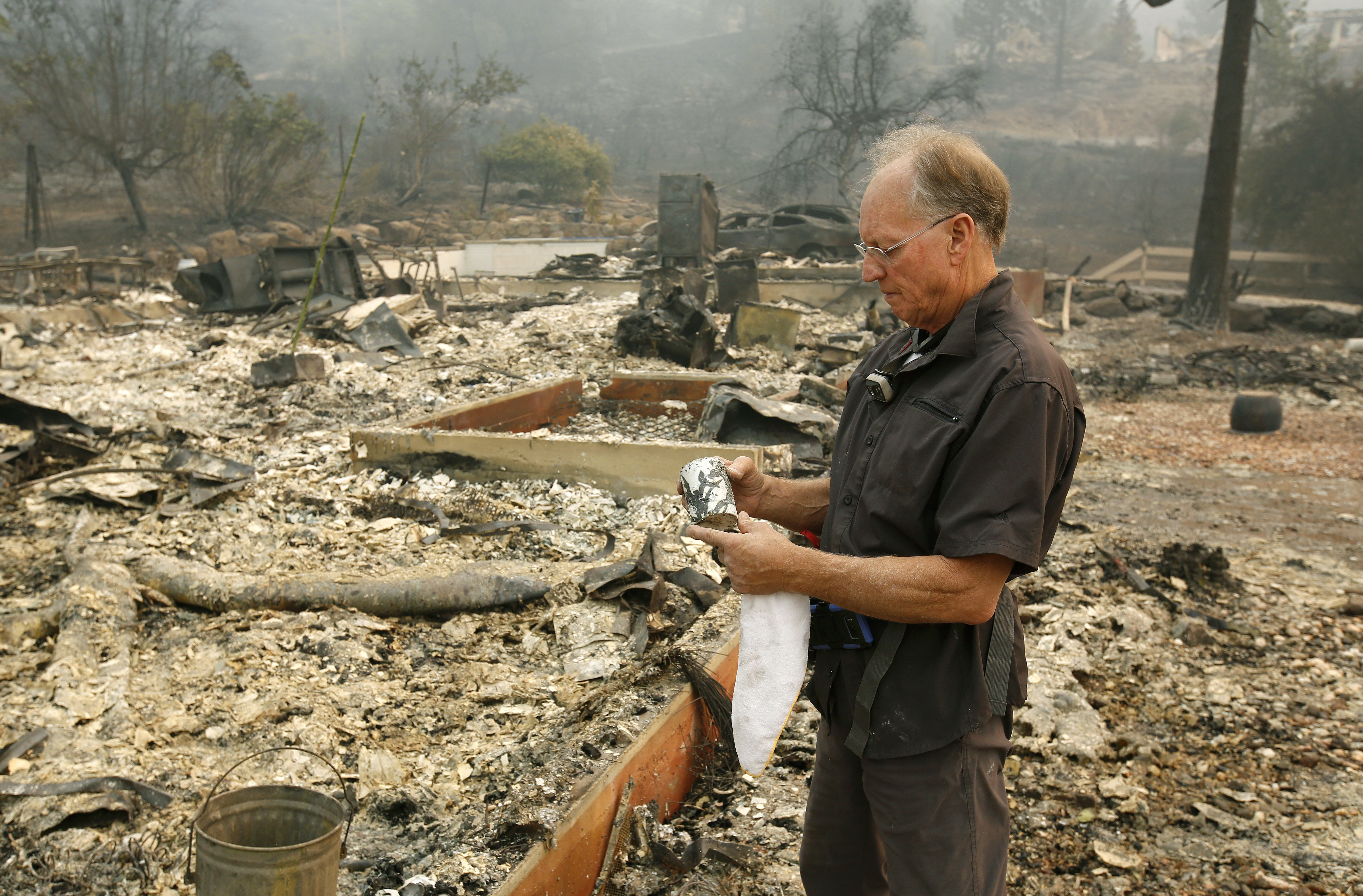 Chuck Rippey看著爸媽的家已成灰燼,手拿著爸媽的杯子不勝唏噓, 他100歲的爸爸Charles Rippey和98歲的媽媽 Sara,在納帕這場大火中,因無法逃離而與家園同歸於「燼」。(美聯社)