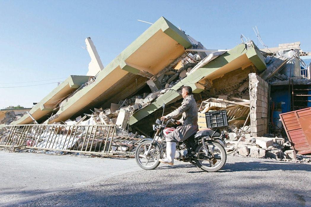 伊拉克蘇萊曼尼亞省居民十三日騎機車行經一棟在前晚強震中被震垮的建築。路透