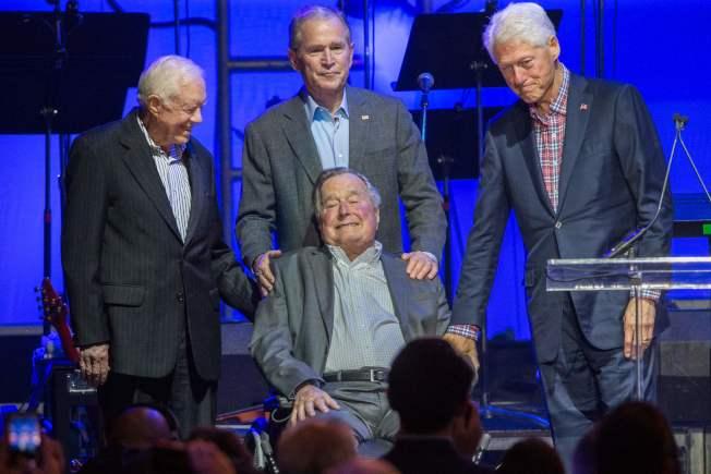 兩位布希總統出版新書,擔心川普拖累共和黨。圖為布希父子(中)日前出席風災籌款晚會。(Getty Images)