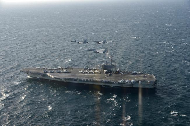 日本自衛隊發布的照片顯示,三架日本戰機正飛越美國航母「雷根號」。(美聯社)