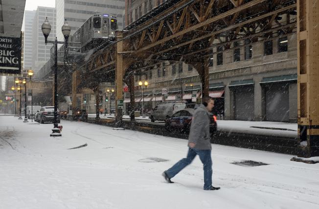 芝加哥居民10日迎來今年立冬以來的第一場雪,氣象預測,受極地渦旋影響,部分民眾將經歷一個「白色感恩節」。圖為一名芝城居民踏雪而行。(美聯社)