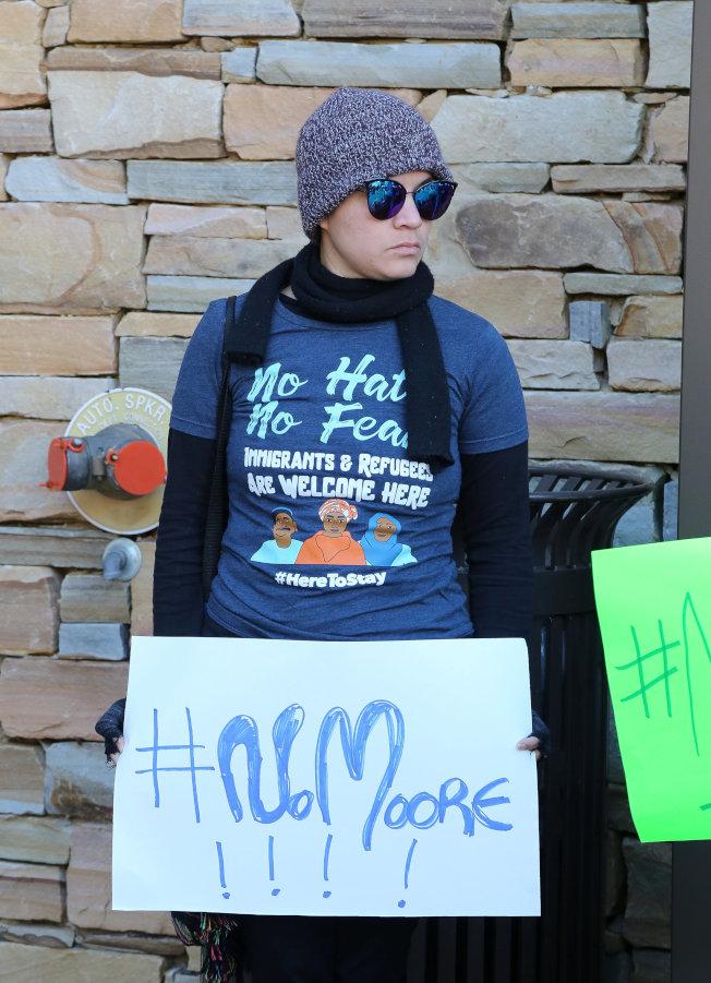 女权团体在退伍军人节早餐会场外担牌抗议,表达对摩尔的不满。 (路透)