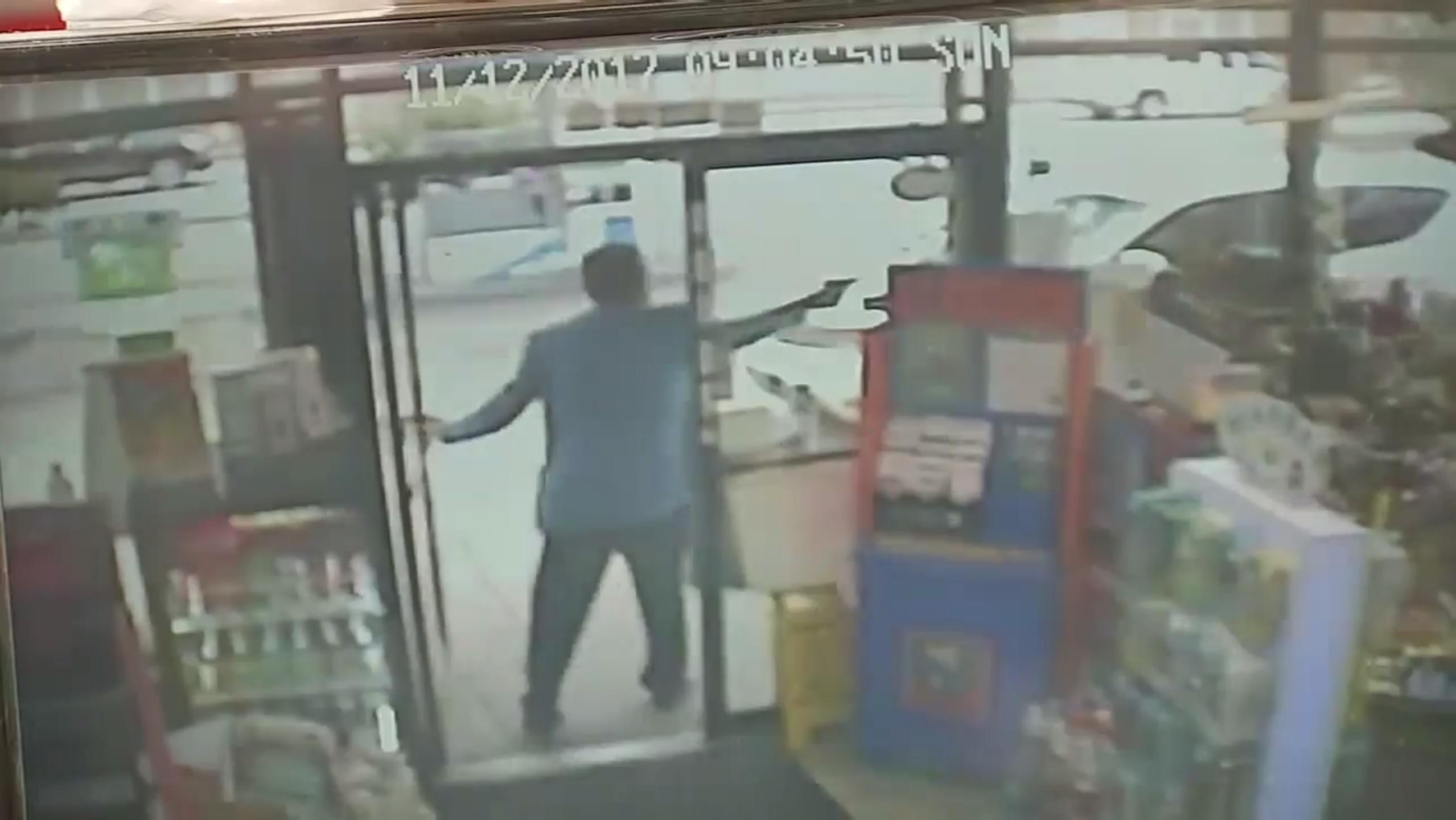 加油站店主負傷後仍持槍追擊歹徒。(取材自監控攝像)