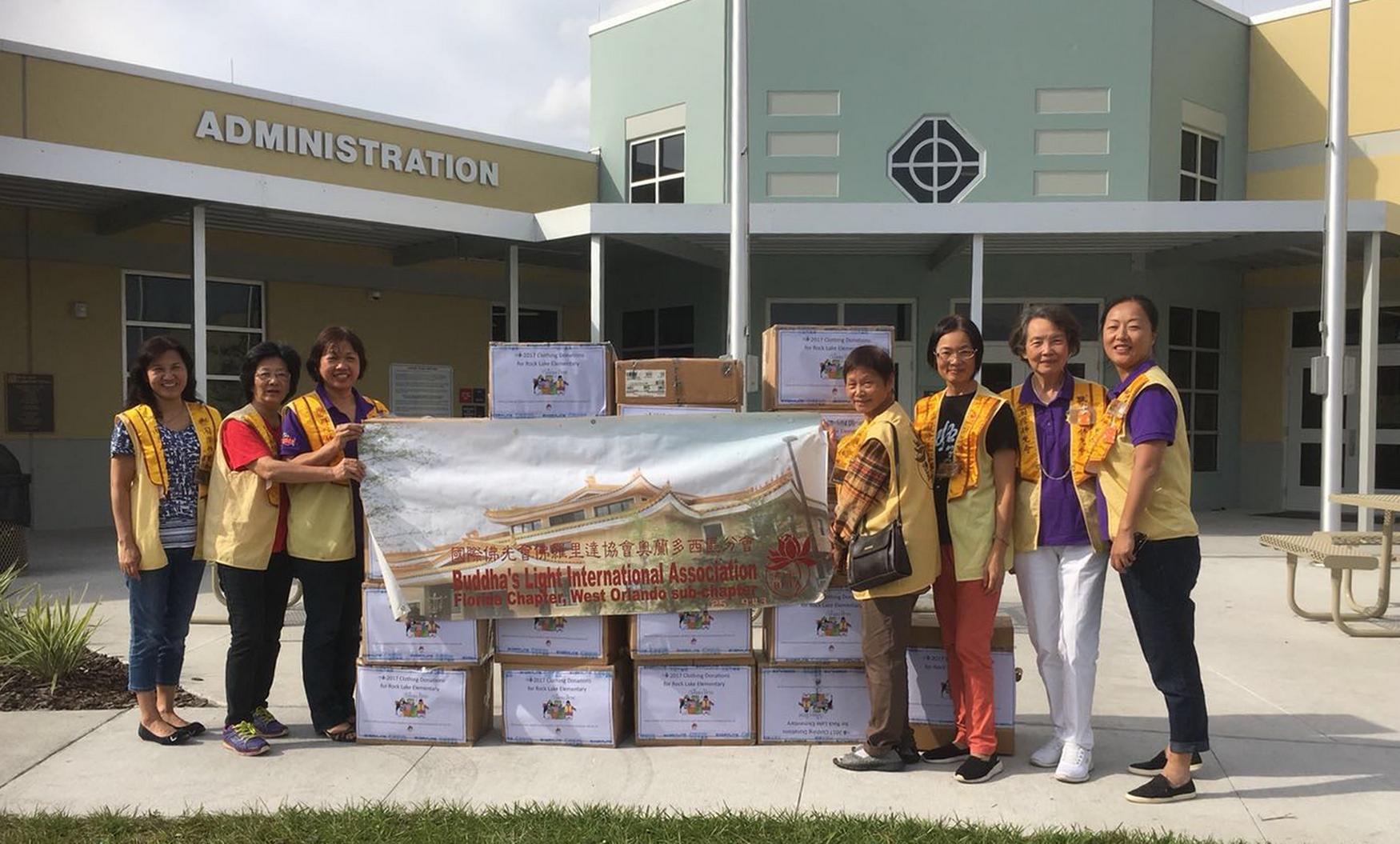 國際佛光會佛州協會奧蘭多西區分會成員送募集的衣物至岩湖小學,右一為西區分會會長鄭曼枝。(鄭曼枝提供)