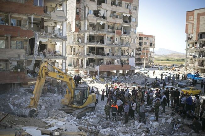 在伊朗薩爾波勒扎哈卜,救援人員14日搜尋倖存者。(新華社)