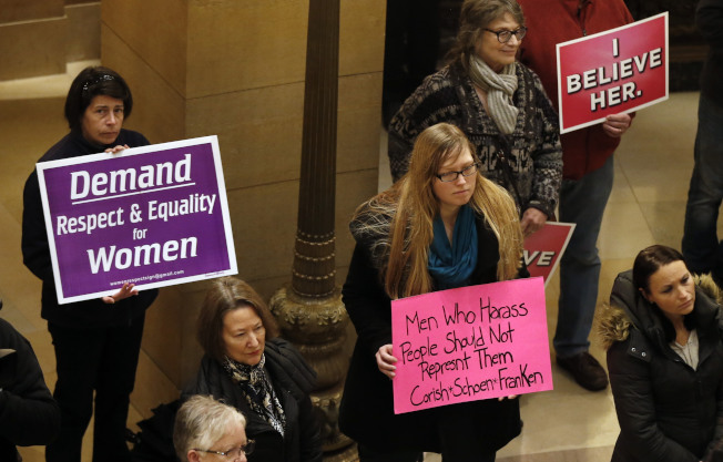 婦女手持標語走進明尼蘇達州議會,抗議兩名州議員及明州選出的國會參議員法蘭肯涉及性騷擾。(美聯社)