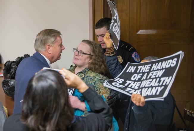 共和黨籍國會參議員(左)欲走進會議室,遭到抗議者阻攔。(Getty Images)