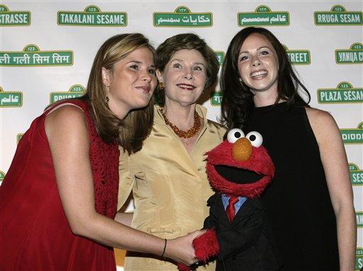 美國前第一夫人蘿拉布希與她的兩位女兒與Elmo合影。艾蒙在1980年才開始出現在「芝麻街」中。很多人都被它圓圓的眼睛、大大的鼻子、天真無邪、說話像小孩子一樣可愛的特徵給吸引。美聯社2007年檔案照