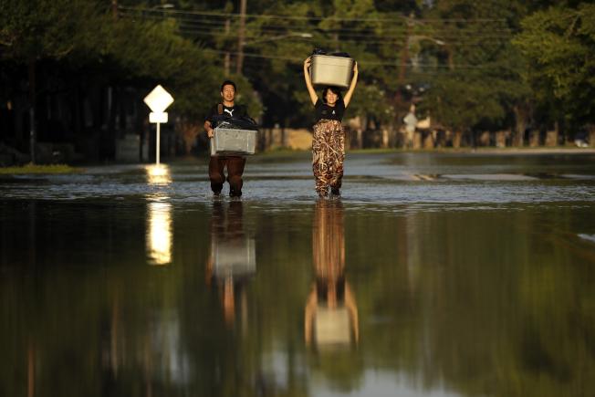 颶風哈維重創休士頓,兩名居民從被洪水淹沒的家中將物品搬出。今年的颶風季終於結束。(美聯社)