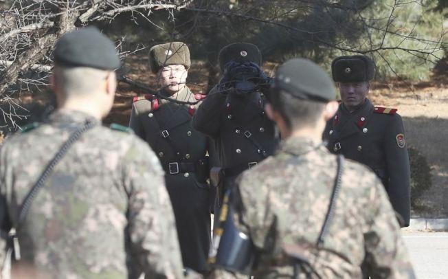 三名北韓士兵在脫北士兵越過國界處與兩名南韓士兵對看。(美聯社)