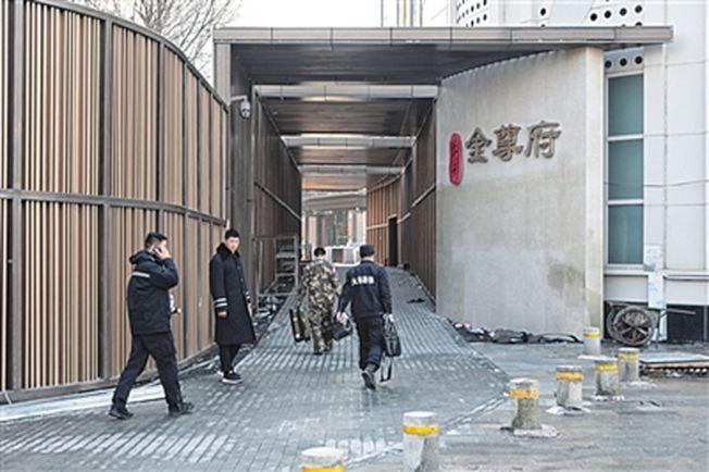 天津市河西區地標性大廈第38層1日凌晨突發火災,造成10死5傷。圖為勘查人員準備進入事故大樓。(取材自新京報)