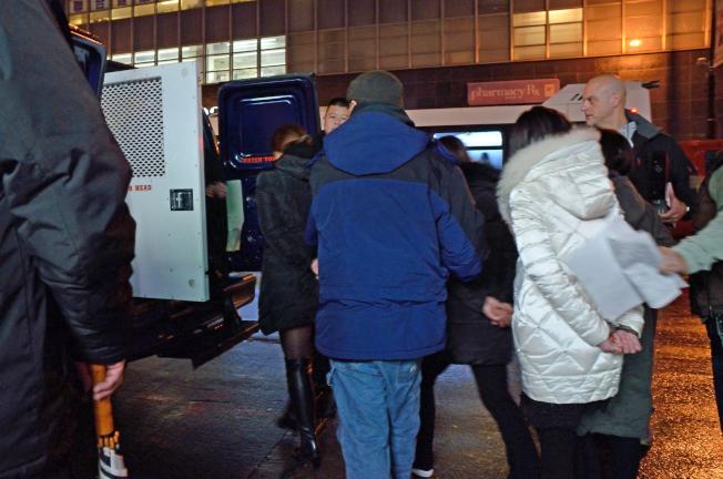 今年1月法拉盛緬街多名華裔色情按摩女被捕,當眾被押上無警徽的廂型車。(本報檔案照)