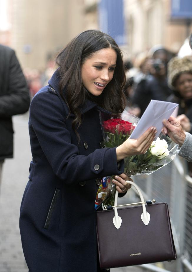 梅根馬克爾沿路收到許多鮮花和禮物,驚喜感動表情寫在臉上。(美聯社)