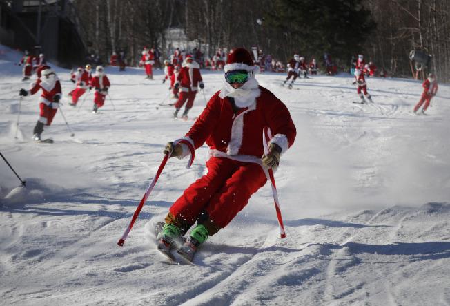 全美許多地區這周將遭受暴風雪或寒流侵襲。圖為緬因州一處滑雪場3日舉行滑雪客裝扮聖誕老人的慈善募款活動。(美聯社)