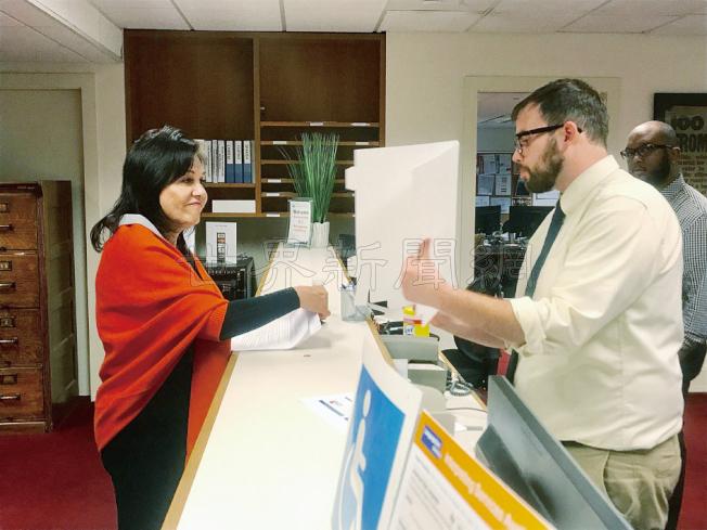 舊金山選務處競選服務部經理Gregory P. Slocum(右)向杜麗莎(左)解釋市長罷免申請程序。(記者黃少華/攝影)