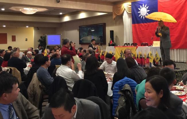 主持人謝啟宇(右)義賣新黨的大黃傘,他形容傘的強度象徵新黨,8級強風也吹不垮。(特派員許惠敏/攝影)