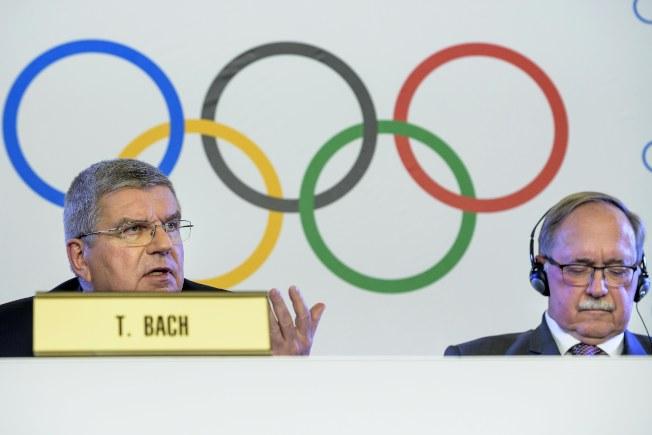 國際奧會主席巴赫(左)宣布禁止俄羅斯參加明年平昌冬奧,右為調查委員會主席施密德。(歐新社)