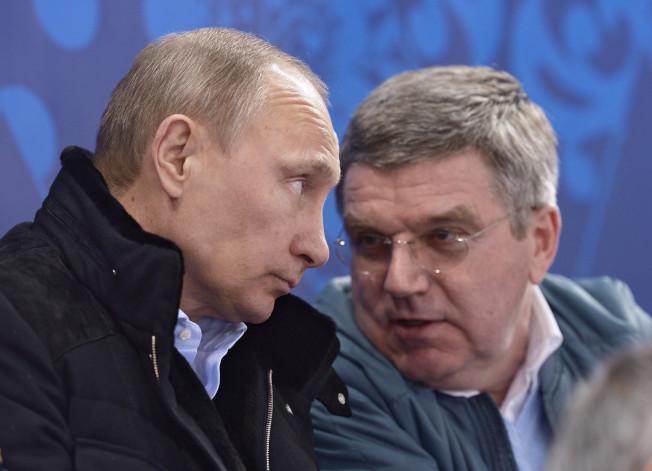 國際奧會主席巴赫(右)在索契冬奧會閉幕式上與俄羅斯總統普亭交談。(美聯社)