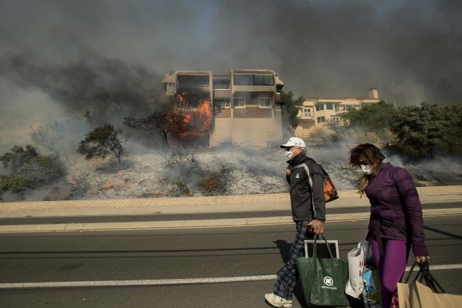 加州范杜拉縣兩位居民拎著從被焚毀公寓中遷移出的物品。(美聯社)