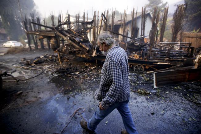 加州湖景露台一位男子走過他的被燒毀的露營車殘骸。(美聯社)