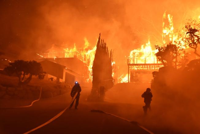 加州范杜拉縣消防局消防員正在全力滅火。(美聯社)