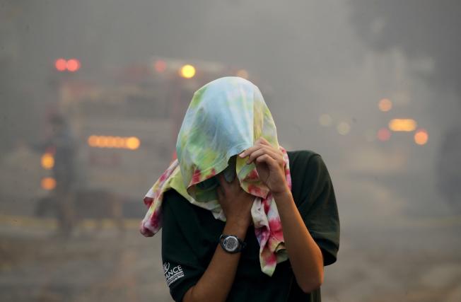 加州湖景露台一位居民用衣物蒙住頭部,防止吸入灰塵。(美聯社)