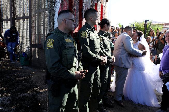 美國邊界巡邏隊上月中旬在提璜納附近打開邊界大門,讓分居兩國的家庭能見上一面。圖為美國新郎把握機會親吻他的墨西哥新娘。(路透)