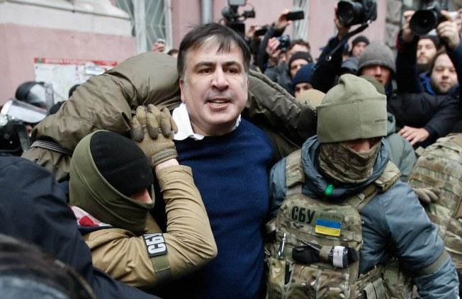 烏克蘭蒙面保安部人員5日闖入喬治亞前總統卡希維利(中)在基輔的家中逮人。(路透)