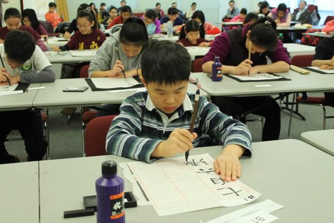 校際書法比賽參賽小朋友聚精會神寫字。(僑教中心提供)